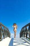 Mujer atractiva en el bikini blanco que se coloca en el pequeño puente en día soleado Foto de archivo