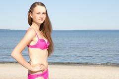 Mujer atractiva en el bikini que presenta en la playa Fotografía de archivo libre de regalías