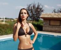 Mujer atractiva en el bikini que presenta en piscina Foto de archivo libre de regalías