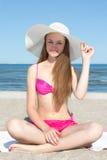 Mujer atractiva en el bikini que se sienta en la playa Foto de archivo