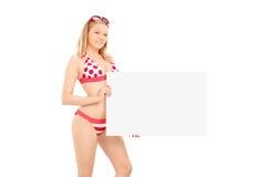 Mujer atractiva en el bikini que sostiene una bandera en blanco imagen de archivo libre de regalías