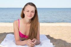 Mujer atractiva en el bikini rosado que miente en la playa Imagen de archivo