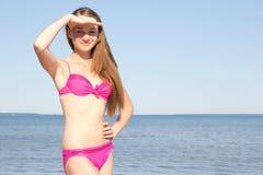Mujer atractiva en el bikini rosado que presenta en la playa Fotos de archivo libres de regalías