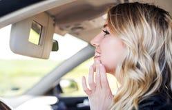 Mujer atractiva en el coche que mira en el espejo del coche Imagenes de archivo