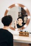 Mujer atractiva en el espejo en estudio de la belleza Imagen de archivo