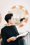 Mujer atractiva en el espejo en estudio de la belleza Imágenes de archivo libres de regalías