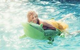 Mujer atractiva en el mar con el colch?n inflable Cuero y muchacha del cocodrilo de la moda en agua Rel?jese en piscina de lujo imagenes de archivo