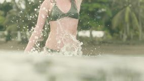 Mujer atractiva en el mar que salpica el agua y que presenta a la cámara Muchacha sonriente que se divierte en agua de mar en la  almacen de metraje de vídeo