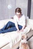 Mujer atractiva en el sofá que alimenta su perro Foto de archivo