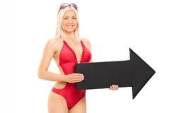 Mujer atractiva en el traje de baño que sostiene una flecha negra que señala el righ Imagenes de archivo