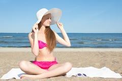 Mujer atractiva en el traje de baño rosado que se sienta en la playa Fotos de archivo
