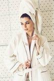 Mujer atractiva en el traje y la toalla blancos en fondo de la teja Fotografía de archivo