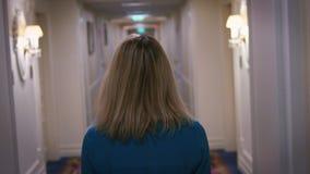 Mujer atractiva en el vestido azul que busca el sitio en hotel de apartamento del pasillo almacen de metraje de vídeo