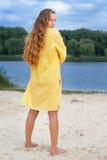 Mujer atractiva en equipo amarillo en la playa del río fotos de archivo