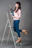 Mujer atractiva en escalera con el taladro pesado Foto de archivo libre de regalías