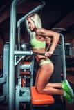 Mujer atractiva en gimnasio en la máquina del entrenamiento Imagen de archivo libre de regalías