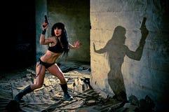 Mujer atractiva en juego escaso con una arma de mano Fotos de archivo libres de regalías