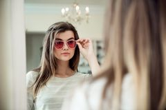 Mujer atractiva en la caza para las nuevas cosas de moda Retrato interior de la mujer caucásica joven elegante en tienda del ópti Imagen de archivo