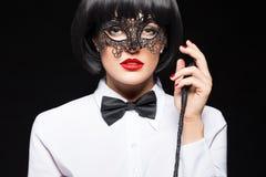 Mujer atractiva en la peluca que presenta con el azote fotografía de archivo libre de regalías