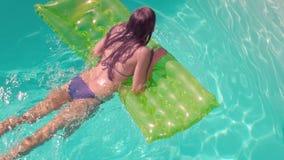Mujer atractiva en la piscina con lilo almacen de metraje de vídeo