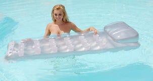 Mujer atractiva en la piscina que sostiene su colchón de aire metrajes