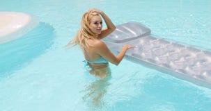 Mujer atractiva en la piscina que sostiene su colchón de aire almacen de video