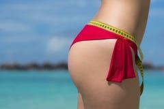 Mujer atractiva en la playa en bikini con la cinta de la medida El concepto Imagen de archivo
