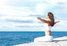 Mujer atractiva en la ropa deportiva blanca que hace yoga en un de madera Fotos de archivo