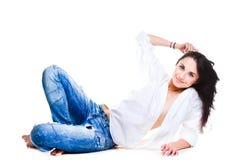 Mujer atractiva en los tejanos que mienten en el suelo blanco Imagenes de archivo
