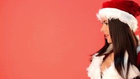 Mujer atractiva en Santa Claus Costume Looking Her Right sobre rojo almacen de video