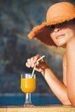 Mujer atractiva en sombrero con el vidrio de zumo de naranja Fotos de archivo libres de regalías