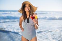 Mujer atractiva en traje de baño con el sombrero de paja que sostiene el cóctel Foto de archivo libre de regalías