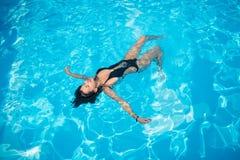 Mujer atractiva en un bañador negro que flota en ella detrás en la piscina y que se relaja imagen de archivo
