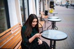Mujer atractiva en un café de la calle que lee un mensaje de texto de su teléfono imagenes de archivo