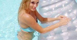 Mujer atractiva en un colchón flotante en la piscina almacen de metraje de vídeo
