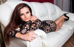 Mujer atractiva en un sofá de cuero Fotos de archivo