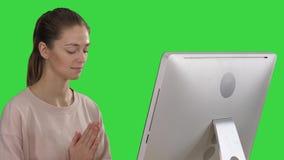 Mujer atractiva en una silla en la tabla con el ordenador que reflexiona sobre una pantalla verde, llave de la croma almacen de video