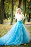 Mujer atractiva en vestido azul largo en parque rubio Fotos de archivo