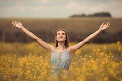 mujer atractiva en vestido en el campo de flor imagen de archivo