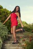 Mujer atractiva en vestido rojo que sonríe tocando su tacón de aguja Imagen de archivo libre de regalías