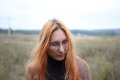 Mujer atractiva en vidrios con el pelo rojo en el prado del otoño Imágenes de archivo libres de regalías