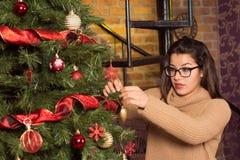 Mujer atractiva en vidrios que adorna el árbol de navidad Foto de archivo libre de regalías