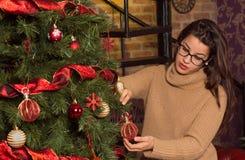 Mujer atractiva en vidrios que adorna el árbol de navidad Imágenes de archivo libres de regalías