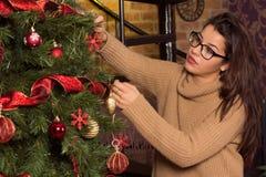 Mujer atractiva en vidrios que adorna el árbol de navidad Fotografía de archivo libre de regalías