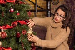 Mujer atractiva en vidrios que adorna el árbol de navidad Fotos de archivo libres de regalías