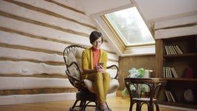Mujer atractiva en vidrios usando smartphone en ático almacen de video