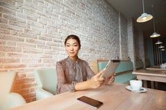 Mujer atractiva feliz que mira los vídeos divertidos mientras que hojea las páginas de Internet en su tableta digital imágenes de archivo libres de regalías