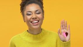 Mujer atractiva feliz que muestra la palma en forma de corazón del confeti, símbolo del amor, caridad almacen de video