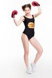 Mujer atractiva feliz que presenta en guantes negros del swimsut y de boxeo Imágenes de archivo libres de regalías
