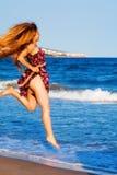 Mujer atractiva feliz que salta en la playa imágenes de archivo libres de regalías